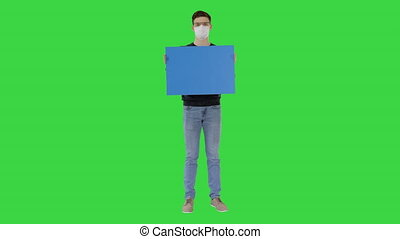 Wide shot. Mockup blue screen. Student in medical mask holding blank placard on a Green Screen, Chroma Key. Professional shot in 4K resolution. 53. You can use it e.g. in your medical, commercial video, business, presentation, broadcast