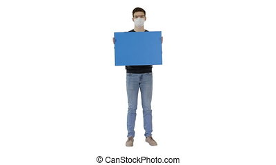 Wide shot. Mockup blue screen. Student in medical mask holding blank placard on white background. Professional shot in 4K resolution. 53. You can use it e.g. in your medical, commercial video, business, presentation, broadcast