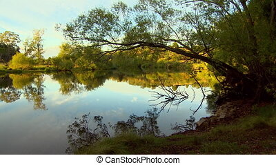 Wide shot of a mirror-like lake at sunset - Wide shot...