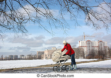 Wide shot of happy young mother in red coat with baby in buggy walking in winter park