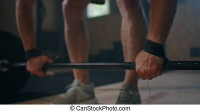 Wide shot of young Caucasian extreme weightlifting athlete man working out with heavy barbell in large hardcore gym hall. High quality 4k footage