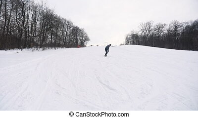 Snowboarder Skiing Downhill - Wide Shot of Young Snowboarder...