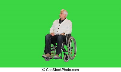 Wide shot. Old man sitting alone in a wheelchair and waiting on a Green Screen, Chroma Key. Professional shot in 4K resolution. 064. You can use it e.g. in your medical, commercial video, business, presentation, broadcast