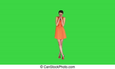 Wide shot. Shocked or surprised young woman in orange sundress on a Green Screen, Chroma Key. Professional shot in 4K resolution. 023. You can use it e.g. in your commercial video, business, presentation, broadcast