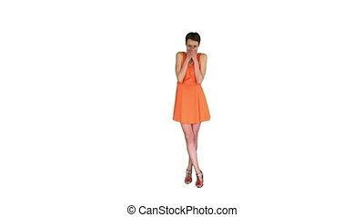 Wide shot. Shocked or surprised young woman in orange sundress on white background. Professional shot in 4K resolution. 023. You can use it e.g. in your commercial video, business, presentation, broadcast