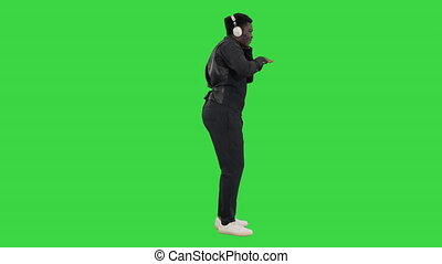 Wide shot. Side view. African american man holding headphones with both hands and grooving to music while looking at camera with a smile on a Green Screen, Chroma Key. Professional shot in 4K resolution. 051. You can use it e.g. in your medical, commercial video, business, presentation, broadcast