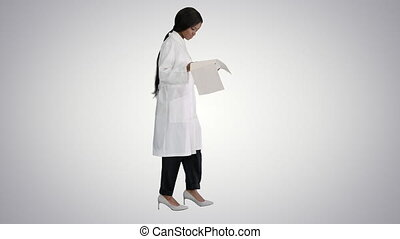 Wide shot. Side view. Afro american doctor woman walking and looking at cardiogram record on gradient background. Professional shot in 4K resolution. 4151. You can use it e.g. in your commercial video, business, presentation, broadcast