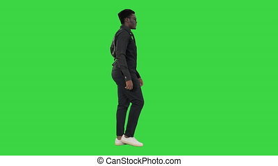 Wide shot. Side view. Afroamerican Jazz Musician with Trumpet Walking and Playing on a Green Screen, Chroma Key. Professional shot in 4K resolution. 4151. You can use it e.g. in your commercial video, business, presentation, broadcast