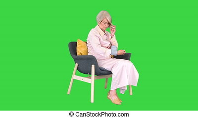 Wide shot. Side view. Aged woman measuring blood pressure Reaction on a high or low pressure on a Green Screen, Chroma Key. Professional shot in 4K resolution. 063. You can use it e.g. in your medical, commercial video, business, presentation, broadcast