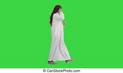 Wide shot. Side view. Arab sheikh making a call walking on a Green Screen, Chroma Key. Professional shot in 4K resolution. 044. You can use it e.g. in your medical, commercial video, business, presentation, broadcast