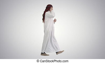 Wide shot. Side view. Arab sheikh making a call walking on gradient background. Professional shot in 4K resolution. 044. You can use it e.g. in your medical, commercial video, business, presentation, broadcast