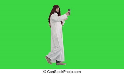Arabian man walking and making a selfie with his phone on a Green Screen, Chroma Key.