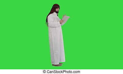Wide shot. Side view. Arabic business man with tablet on a Green Screen, Chroma Key. Professional shot in 4K resolution. 044. You can use it e.g. in your medical, commercial video, business, presentation, broadcast