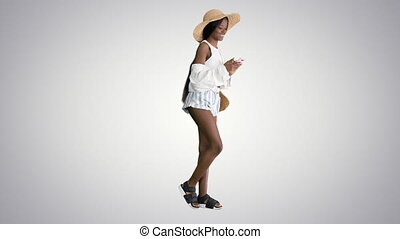 Wide shot. Side view. Attractive young african woman in summer dress using mobile phone on gradient background. Professional shot in 4K resolution. 4151. You can use it e.g. in your commercial video, business, presentation, broadcast