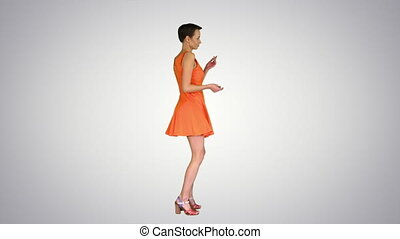 Wide shot. Side view. Beautiful woman dances in flirty orange dress on gradient background. Professional shot in 4K resolution. 023. You can use it e.g. in your commercial video, business, presentation, broadcast