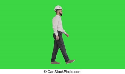 Wide shot. Side view. Businessman in formal wear and white hardhat walking on a Green Screen, Chroma Key. Professional shot in 4K resolution. 044. You can use it e.g. in your medical, commercial video, business, presentation, broadcast