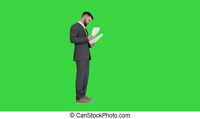 Wide shot. Side view. Businessman standing and reading docs seriously on a Green Screen, Chroma Key. Professional shot in 4K resolution. 044. You can use it e.g. in your medical, commercial video, business, presentation, broadcast
