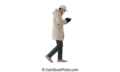 Caucasian man in a medical mask walking and using the phone on white background.
