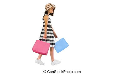 Wide shot. Side view. Cute little girl walking with shopping bags on white background. Professional shot in 4K resolution. 062. You can use it e.g. in your medical, commercial video, business, presentation, broadcast