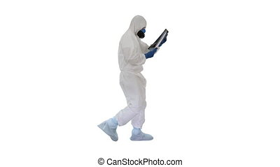Doctor in protective suit looking at lungs x-ray while walking on white background.