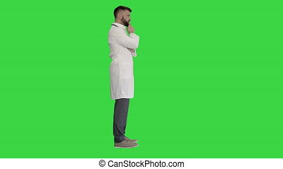 Doctor standing and thinking hard on a Green Screen, Chroma Key.