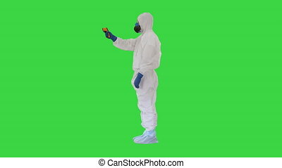 Doctor wearing protective clothes using infrared forehead thermometer to check body temperature for virus symptoms on a Green Screen, Chroma Key.