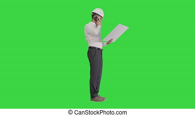 Wide shot. Side view. Engineer in formalwear and hardhat talking to client or contractor on mobile phone and looking at blueprint on a Green Screen, Chroma Key. Professional shot in 4K resolution. 044. You can use it e.g. in your medical, commercial video, business, presentation, broadcast