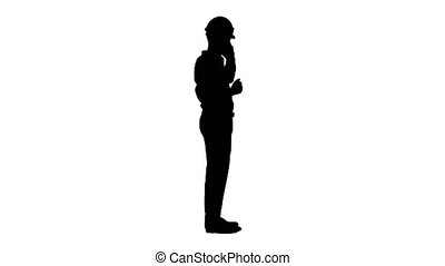 Wide shot. Side view. Engineer in white hard hat talking on his mobile phone, Alpha Channel Professional shot in 4K resolution. 044. You can use it e.g. in your medical, commercial video, business, presentation, broadcast