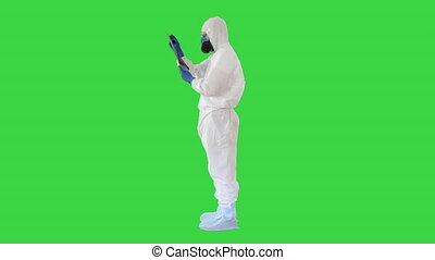 Wide shot. Side view. Epidemiologist in respirator examine the patient's pneumonia on a radiograph Covid-19 on a Green Screen, Chroma Key. Professional shot in 4K resolution. 53. You can use it e.g. in your medical, commercial video, business, presentation, broadcast