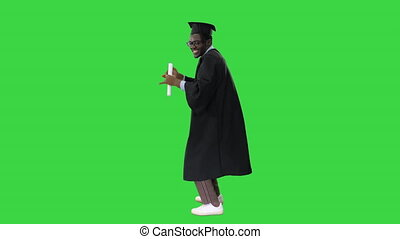 Wide shot. Side view. Excited african american male student in graduation robe dancing happily with his diploma on a Green Screen, Chroma Key. Professional shot in 4K resolution. 051. You can use it e.g. in your medical, commercial video, business, presentation, broadcast