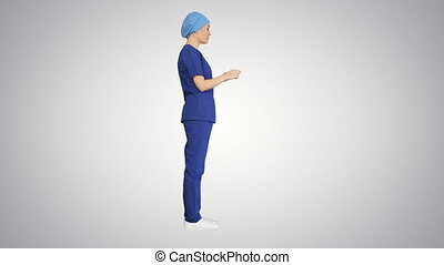 Wide shot. Side view. Female doctor in blue uniform talking about medical care on gradient background. Professional shot in 4K resolution. 043. You can use it e.g. in your medical, commercial video, business, presentation, broadcast