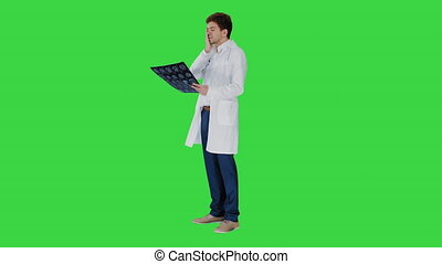 Wide shot. Side view. Frustrated male doctor examining computed tomography scan of brain on a Green Screen, Chroma Key. Professional shot in 4K resolution. 047. You can use it e.g. in your medical, commercial video, business, presentation, broadcast