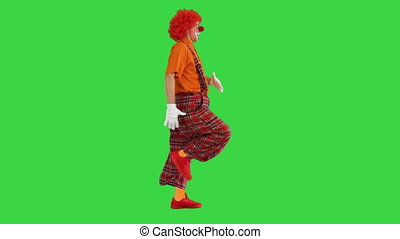 Wide shot. Side view. Funny clown walking like he is marching on a parade on a Green Screen, Chroma Key. Professional shot in 4K resolution. 061. You can use it e.g. in your medical, commercial video, business, presentation, broadcast