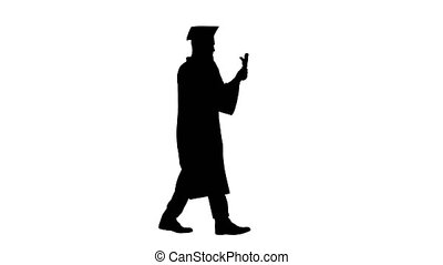 Wide shot. Side view. Graduating student walking and making a call, Alpha Channel Professional shot in 4K resolution. 044. You can use it e.g. in your medical, commercial video, business, presentation, broadcast