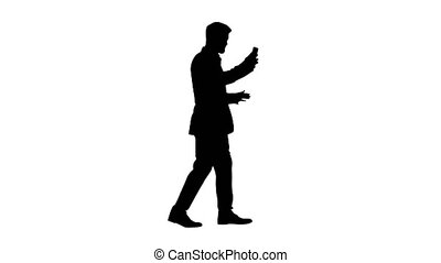 Wide shot. Side view. Handsome businessman walking and recording vlog on his phone, Alpha Channel Professional shot in 4K resolution. 044. You can use it e.g. in your medical, commercial video, business, presentation, broadcast