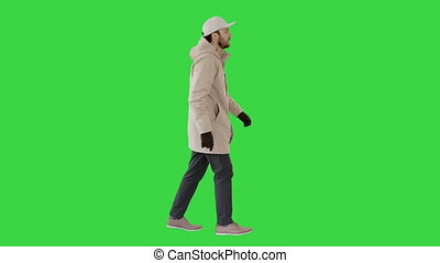 Handsome fashionable man in a winter stylish coat walking on a Green Screen, Chroma Key.