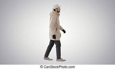 Handsome fashionable man in a winter stylish coat walking on gradient background.