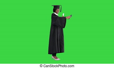 Wide shot. Side view. Happy African American female graduate holding diploma and making selfie on a Green Screen, Chroma Key. Professional shot in 4K resolution. 046. You can use it e.g. in your medical, commercial video, business, presentation, broadcast
