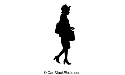 Wide shot. Side view. Happy african american woman in hat and knitwear walking with shopping bags, Alpha Channel Professional shot in 4K resolution. 046. You can use it e.g. in your medical, commercial video, business, presentation, broadcast