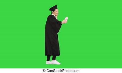 Wide shot. Side view. Happy female graduate in mortarboard making selfie on her phone on a Green Screen, Chroma Key. Professional shot in 4K resolution. 043. You can use it e.g. in your medical, commercial video, business, presentation, broadcast