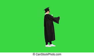 Wide shot. Side view. Happy graduate woman holding diploma and thumb up on a Green Screen, Chroma Key. Professional shot in 4K resolution. 043. You can use it e.g. in your medical, commercial video, business, presentation, broadcast