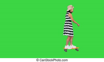 Wide shot. Side view. In and out of the frame. Happy little girl riding a skateboard on a Green Screen, Chroma Key. Professional shot in 4K resolution. 062. You can use it e.g. in your medical, commercial video, business, presentation, broadcast