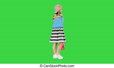 Wide shot. Side view. Little asian girl in a sundress and a hat posing with shopping bags on a Green Screen, Chroma Key. Professional shot in 4K resolution. 062. You can use it e.g. in your medical, commercial video, business, presentation, broadcast