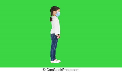 Little girl taking her face mask off and smiling at camera ...