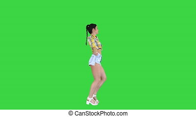 Wide shot. Side view. Magnificent sweet girl in jeans shorts, sneakers, dancing on a Green Screen, Chroma Key. Professional shot in 4K resolution. 021. You can use it e.g. in your commercial video, business, presentation, broadcast