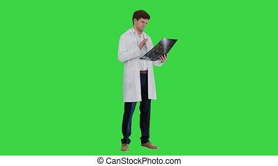 Wide shot. Side view. Male doctor checking computed tomography and looking at someone approvingly on a Green Screen, Chroma Key. Professional shot in 4K resolution. 047. You can use it e.g. in your medical, commercial video, business, presentation, broadcast