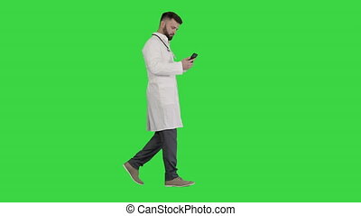 Wide shot. Side view. Male doctor in white medical uniform walking and using smartphone on a Green Screen, Chroma Key. Professional shot in 4K resolution. 044. You can use it e.g. in your medical, commercial video, business, presentation, broadcast