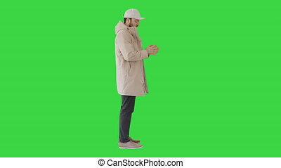 Man in winter clothes using sanitizer spray to prevent flu disease on a Green Screen, Chroma Key.