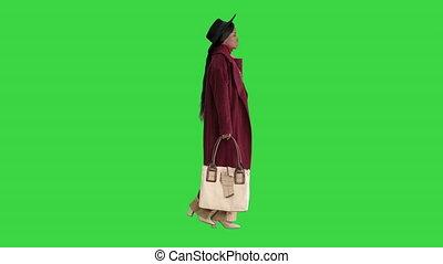 Pretty american woman in a hat walking on a Green Screen, Chroma Key.