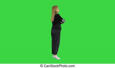 Pretty blonde woman standing with arms crossed on a Green Screen, Chroma Key.